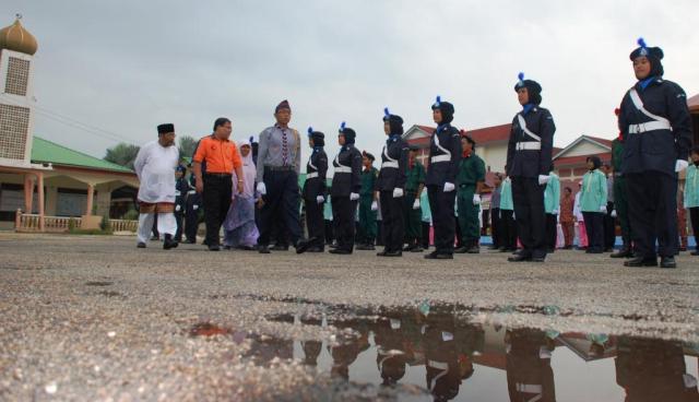 LINTAS HORMAT ...Dua kiri, Tuan Syed Norul Shahrul Bin Syed Nasir, Penolong Pegawai Daerah Batu Pahat, yang mewakili Pegawai Daerah Batu Pahat memeriksa barisan kehormatan 7 badan beruniform SMKPS diketuai Mohd Syafiq Nasir (tiga kiri). Beliau melahirkan rasa gembira kerana dapat menjejakkan kaki di SMKPS dan menyeru para pelajar supaya mengambil iktibar atas kejayaan rakan-rakan mereka dalam bidang akademik dan kokurikulum