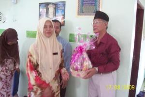Puan Nora Asyikin menyampaikan cenderamata kepada penceramah jemputan, Haji Ishak Zam Zam