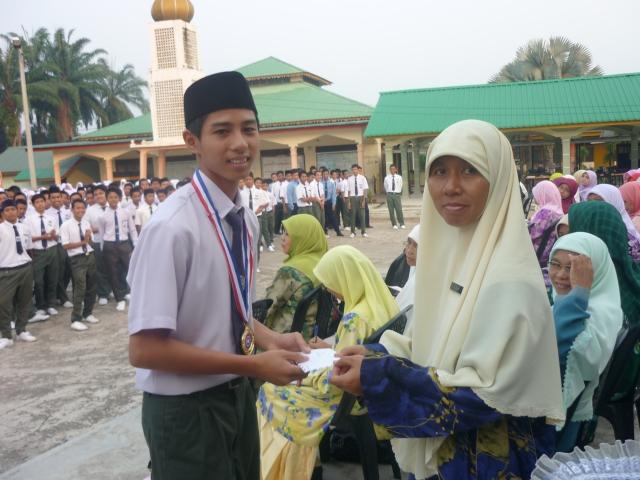 CEMERLANG... Ilham Amin menerima pingat emas dan Insentif Kokurikulum daripada Pengetua SMKPS