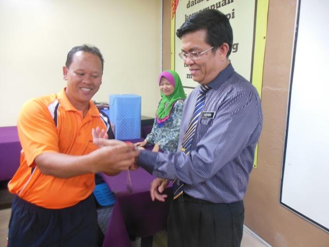 Encik Yasin sedang memakaikan seutas jam tangan hadiah Kebiru kepada Encik Mohsin