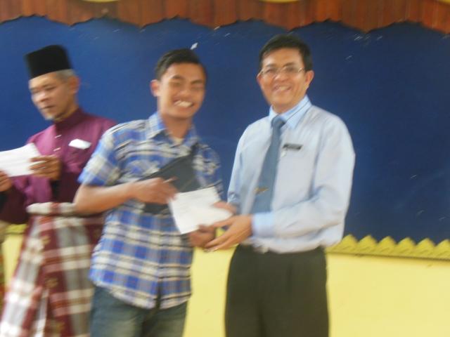 Mohd Izaat menerima slip  SPM daripada Encik Mohsin