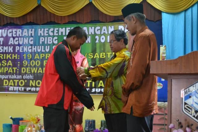 Haji Sudin memakaikan track suit kepada Olahragawan sekolah, Mohd Idris
