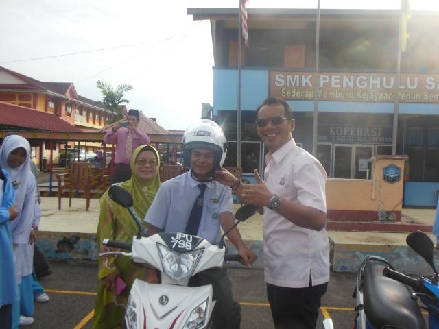 YB Datuk Zulkarnain menyerahkan topi keledar kepada pelajar SMKPS