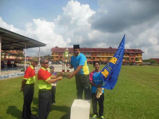 Encik Masli menyampaikan piala pusingan juara kepada ketua rumah Berani